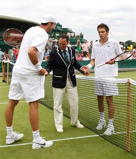 John Isner of the US, left, and Nicolas Mahut of France, right, talk with chair umpire Mohamed Lahyani before resuming their their epic men's singles match at the All England Lawn Tennis Championships at Wimbledon