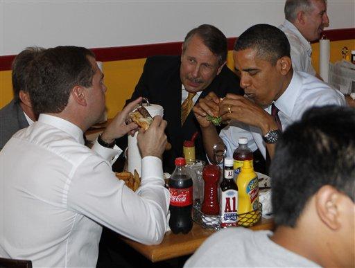 President Barack Obama and Russia's President Dmitry Medvedev, left, eat burgers.