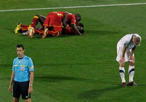 United States' Jay DeMerit, right, reacts as Ghana players, center back, celebrate following the World Cup round of 16 soccer match between the United States and Ghana. (AP Photo/Alessandra Tarantino)
