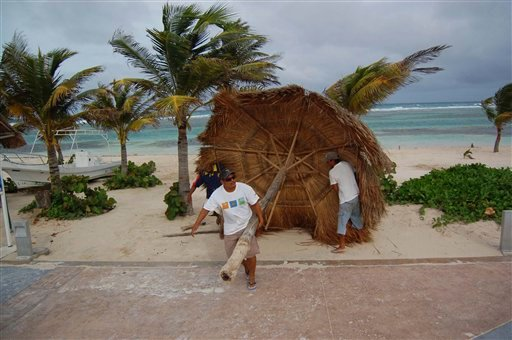 Workers remove a palm shade from the beach in preparation for the arrival of tropical storm Alex as winds begin to increase in Mahaual, Mexico, Saturday, June 26, 2010. (AP Photo/Israel Leal)
