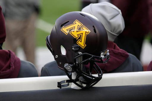 In this Nov. 24, 2012, file photo, a Minnesota helmet hangs on a sideline heater during an NCAA college football game against Michigan State, in Minneapolis.