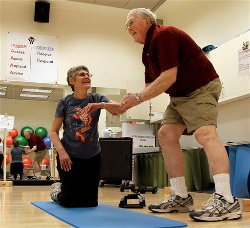 Ed Ritt, right, helps his wife, Bobbie, up after pushups at a couples exercise class for cancer patients, Thursday, June 24, 2010, at Oregon Health and Sciences University in Portland, Ore. (AP Photo/Don Ryan)