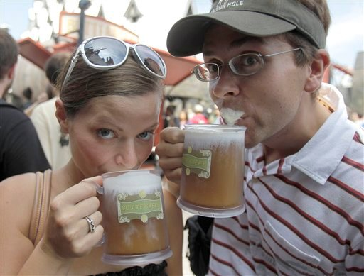 This June 18, 2010 file photo shows park guests Jillian Woodworth, left, and Steven Hopke as they try Butterbeer at the grand opening of the Wizarding World of Harry Potter at Universal Orlando theme park in Orlando, Fla. (AP Photo/John Raoux, FILE)