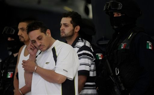 "Jesus Ernesto Chavez, known as ""El Camello"", second from left, stands as he is guarded by a federal police officer during a presentation to the press, in Mexico City, Friday, July 2, 2010.  (AP Photo/Carlos Jasso)"