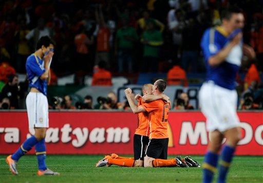 Netherlands' Andre Ooijer, center right, and Netherlands' Wesley Sneijder, center left, celebrate following the World Cup quarterfinal soccer match between the Netherlands and Brazil at Nelson Mandela Bay Stadium. (AP Photo/Martin Meissner)