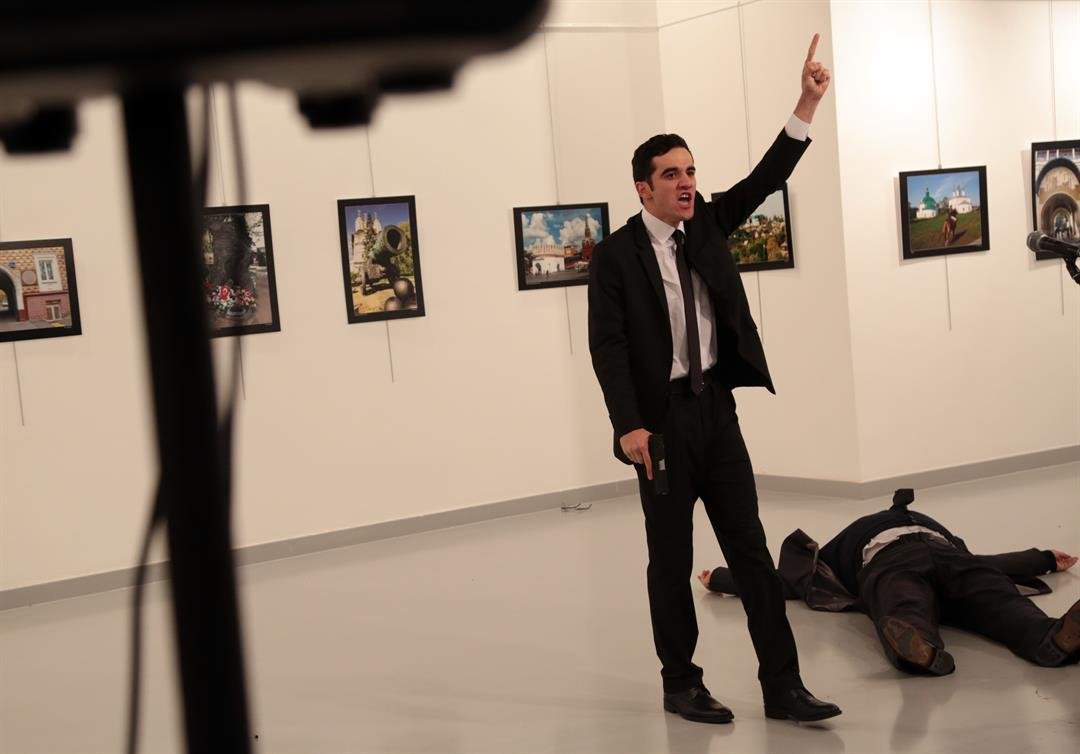 A man gestures near to the body of a man at a photo gallery in Ankara, Turkey, Monday, Dec. 19, 2016. (AP Photo/Burhan Ozbilici)