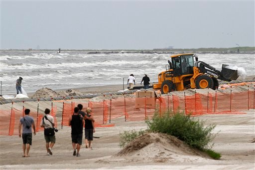 People walk along a beach as workers shovel and bag sand oiled by April's Deepwater Horizon oil rig explosion and spill on a beach in Grand Isle, La. on Monday, July 5, 2010. (AP Photo/Patrick Semansky)