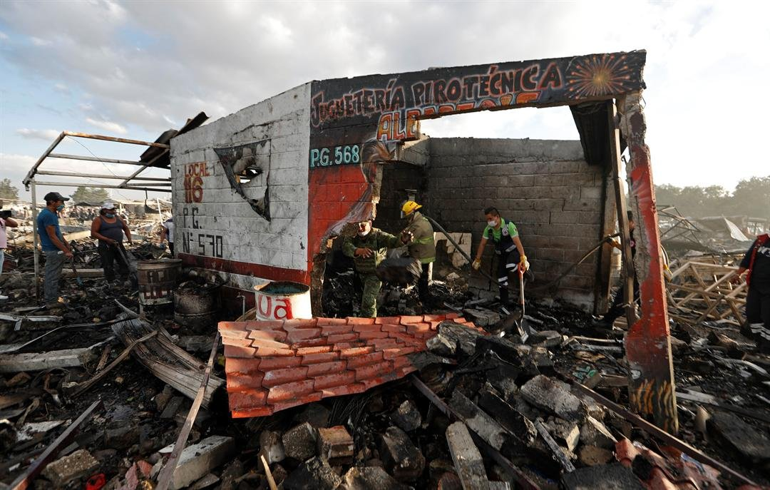 Firefighters and rescue workers remove debris from the scorched ground of Mexico's best-known fireworks market after an explosion explosion ripped through it, in Tultepec, on the outskirts of Mexico City, Mexico, Tuesday, Dec. 20, 2016. AP