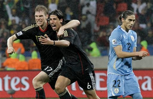 Germany's Sami Khedira, center, celebrates with teammate Germany's Per Mertesacker after scoring his side's third goal during the World Cup third-place soccer match between Germany and Uruguay . (AP Photo/Gero Breloer)