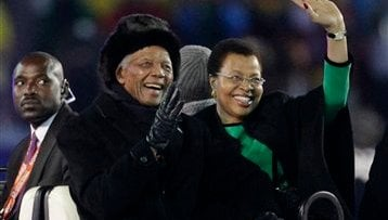 Former South African President Nelson Mandela, left, and his wife Graca Machel, right, wave to spectators as they are driven across the field during the closing ceremony before the World Cup final.  (AP Photo/Matt Dunham)