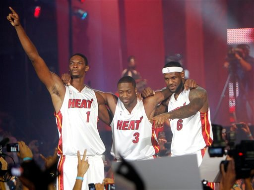 From left, Chris Bosh, Dwyane Wade and LeBron James acknowledge the cheers during a fan event at the American Airlines Arena in Miami.