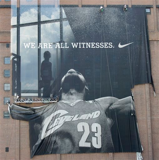 A child is seen reflected in the fifth-floor window of a parking garage across the street from where workers remove the giant banner of former Cleveland Cavaliers basketball star LeBron James in downtown Cleveland.