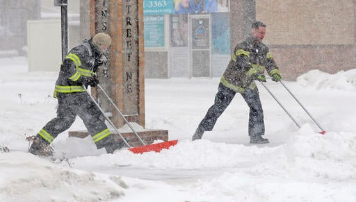Mandan firefighters Shane Weltikol, left, Chad Nicklos clear accumulating snow from outside the firehouse in downtown Mandan, N.D. Dec. 25, 2016. (Tom Stromme/The Bismarck Tribune via AP).