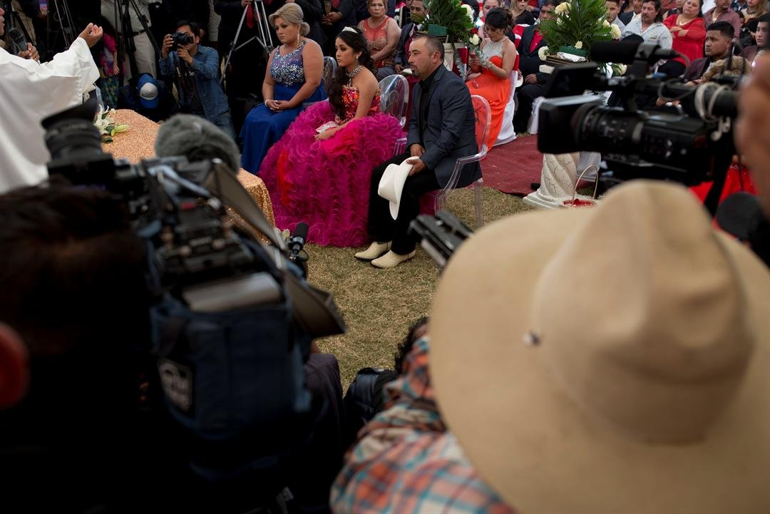 Rubi Ibarra sits next to her mother Anaelda and her father Crescencio during a Mass as part of Rubi's down-home 15th birthday party in the village of La Joya, San Luis Potosi State, Mexico, Monday, Dec. 26, 2016.