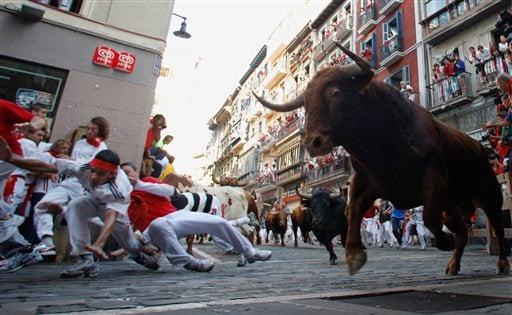 Revelers run on the Estafeta corner in front of El Pilar ranch fighting bulls during the seventh run of the San Fermin fiestas in Pamplona northern Spain, Tuesday July 13, 2010. (AP Photo/Alvaro Barrientos)