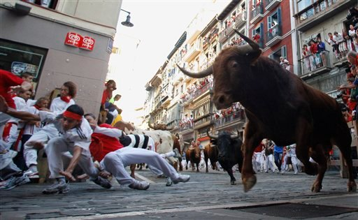 Revelers run on the Estafeta corner in front of El Pilar ranch fighting bulls during the seventh run of the San Fermin fiestas in Pamplona northern Spain, Tuesday July 13, 2010. (AP Photo/Alvaro Barrientos)