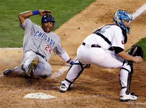 National League's Marlon Byrd, of the Chicago Cubs, scores past American League catcher John Buck, of the Toronto Blue Jays, on a three-run double by Brian McCann, of the Atlanta Braves.