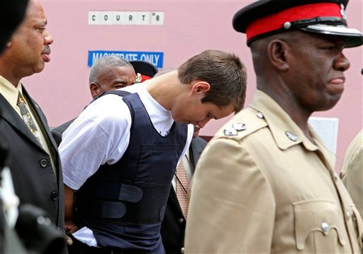 """Colton Harris-Moore, the teenage fugitive police have dubbed the """"Barefoot Bandit,"""" is escorted handcuffed by Bahamian authorities to the court building in Nassau, Tuesday July 13, 2010."""