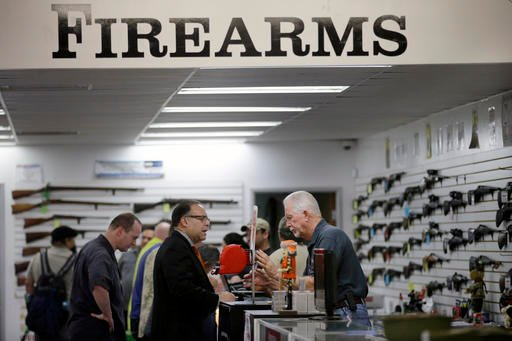 In this Dec. 9, 2015, file photo, sales associate Mike Conway, right, shows Paul Angulo guns at Bullseye Sport gun shop in Riverside, Calif.