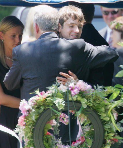 In this June 29, 2006, file photo, John Ramsey hugs his son, Burke, facing camera, at the graves of his wife, Patsy, and daughter JonBenet, during services for his wife at the St. James Episcopal Cemetery in Marietta, Ga.