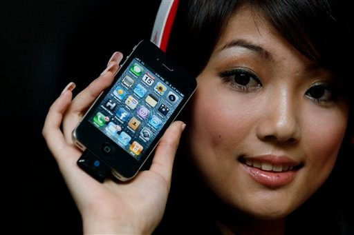 A model holds the latest iPhone 4 with bluetooth device during a promotional event in Hong Kong Thursday, July 15, 2010. (AP Photo/Kin Cheung)