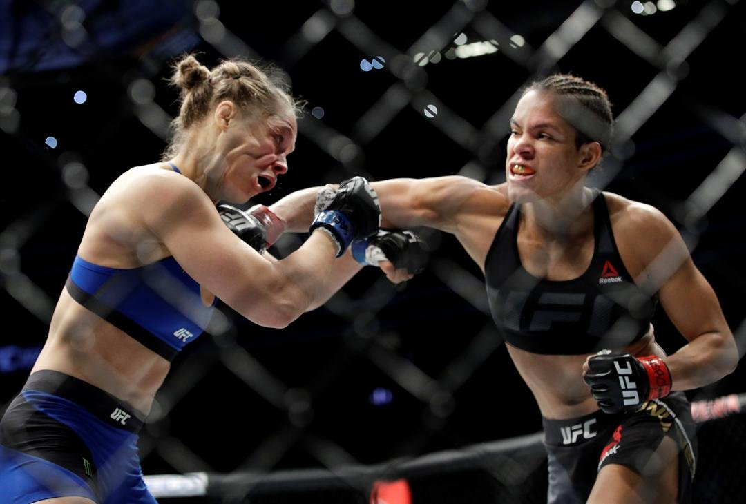 Amanda Nunes, right, connects with Ronda Rousey in the first round of their women's bantamweight championship mixed martial arts bout at UFC 207, Friday, Dec. 30, 2016, in Las Vegas. Nunes won the fight after it was stopped in the first round. (AP Photo/J