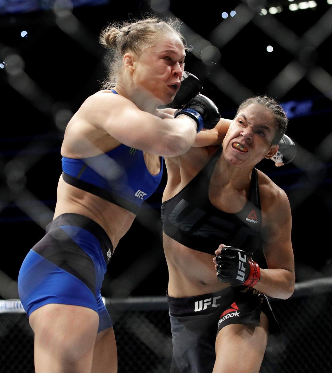 Amanda Nunes, right, connects with Ronda Rousey during the first round of their women's bantamweight championship mixed martial arts bout at UFC 207, Friday, Dec. 30, 2016, in Las Vegas. Nunes won the fight after it was stopped in the first round. (AP Pho