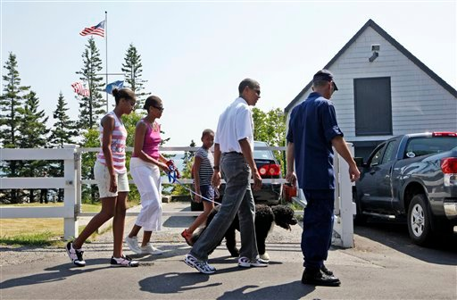 President Barack Obama, first lady Michelle Obama, second from left, daughters Malia, left, and Sasha and dog Bo are greeted by Coast Guard Station chief Tim Chase, right, as they visit Bass Harbor Head Lighthouse. (AP Photo/Charles Dharapak)