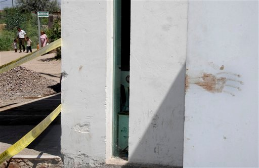 A dark red stain is seen at a wall of a site marked as a crime scene by police at the entrance of a house where a party was interrupted by gunmen early Sunday in the town of Torreon.  (AP Photo)