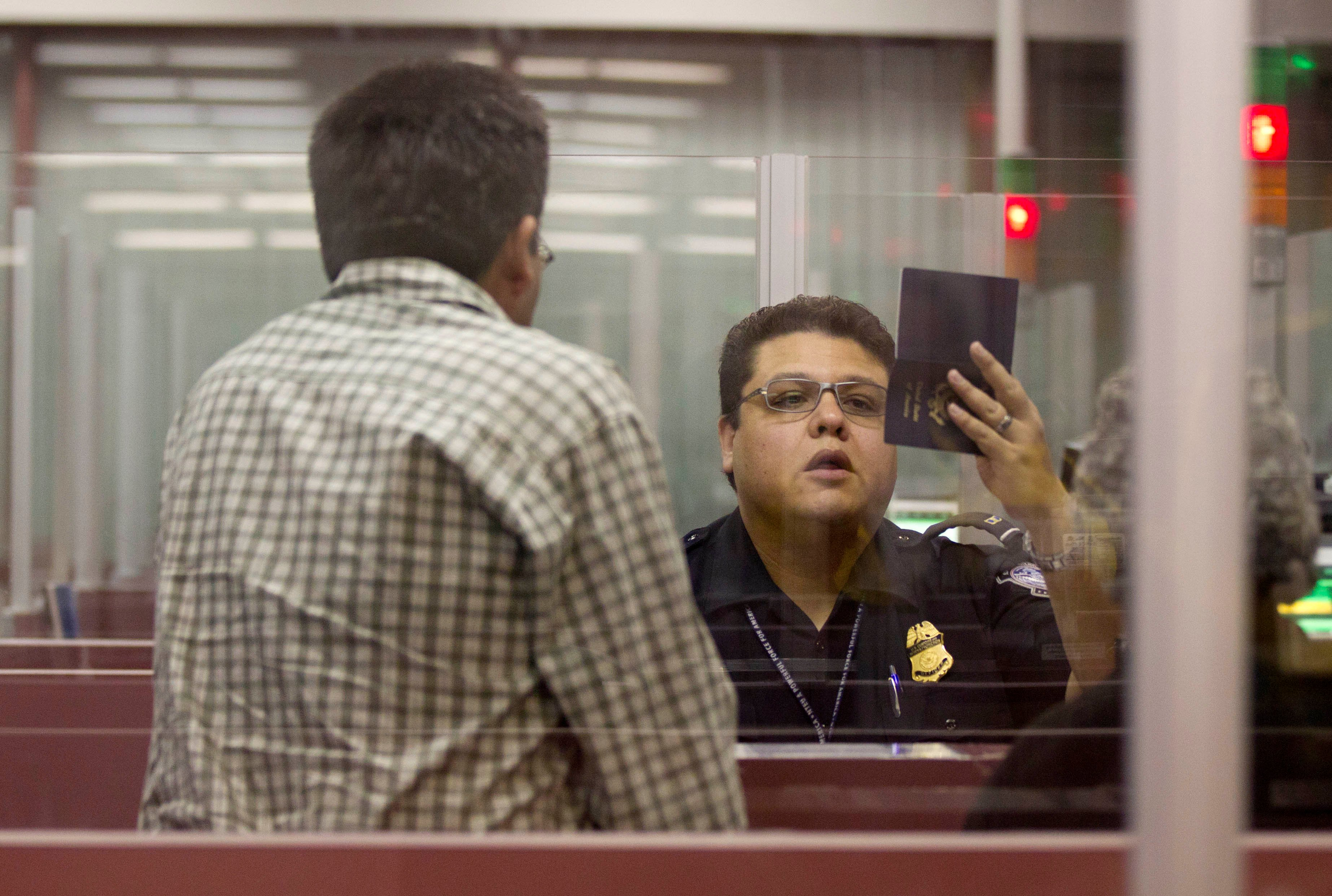 A Customs and Border Protection officer checks the passport of a non-resident visitor to the United States inside immigration control at McCarran International Airport, Tuesday, Dec. 13, 2011, in Las Vegas. (AP Photo/Julie Jacobson)
