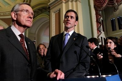 Senate Majority Leader Harry Reid, D-Nev., left, is joined by newly-sworn Sen. Carte Goodwin, D-W.Va., right, after the Senate cleared a hurdle to restore unemployment benefits to millions of Americans who have been out of work for more than six months.