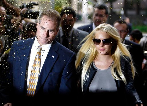 Confetti flies as Lindsay Lohan, with an unidentified man, arrives at the Beverly Hills courthouse Tuesday, July 20, 2010. (AP Photo/Reed Saxon)