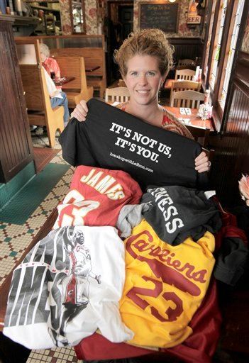 Sitting in front of a pile of discarded shirts honoring former Cleveland Cavaliers NBA star LeBron James, Yours Truly restaurant manager Christina Weiner holds up the t-shirt that is being exchanged for the turned-in tops at the eatery in Beachwood, Ohio.