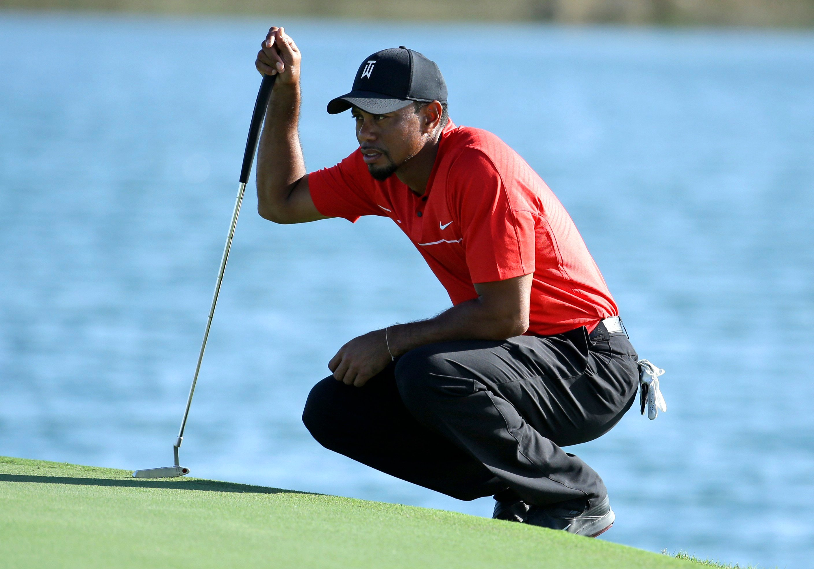FILE - In this Dec. 4, 2016, file photo, Tiger Woods lines up a putt on the 17th hole during the final round of the Hero World Challenge golf tournament in Nassau, Bahamas.  (AP Photo/Lynne Sladky, File)