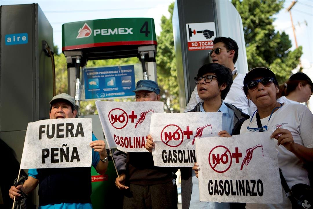 "People hold signs reading ""No more gasoline price hikes"" and ""Pena out,"" as they shut down a Pemex gas station in protest over fuel price increases, in Mexico City, Sunday, Jan. 1, 2017. (AP Photo/Rebecca Blackwell)"