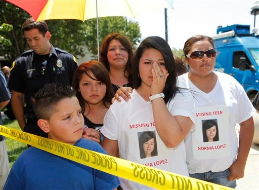 Moreno Valley residents wearing T-shirts of missing teen Norma Lopez, react as authorities confirm that a body was identified through dental records as Norma Lopez.  (AP Photo/Damian Dovarganes)