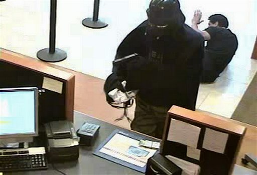 In this photo released July 22, 2010 by the Suffolk County Police Department, a person wearing a Darth Vader mask and cape is captured on surveillance camera robbing a Chase bank in Setauket, N.Y., Thursday, July 22.