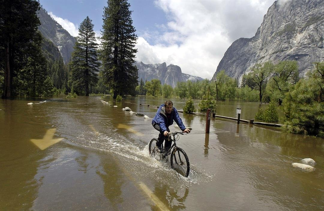 File - In this May 16, 2005, file photo, mountaineering shop worker Chris Stewart bicycles down a flooded Chapel Straight in Yosemite National Park, Calif.