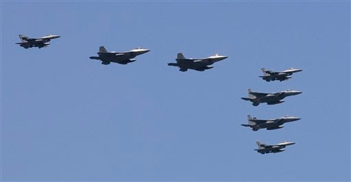 U.S. F-22 stealth fighters, second and third from left, fly with other fighters over the Nimitz-class USS George Washington during joint military exercises between the U.S. and South Korea.