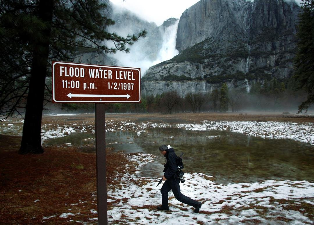 Photographer Michael Macor walks through a flooded Cook's Meadow area near the Merced River as water pours down Yosemite Falls during a media tour in Yosemite National Park, Calif., Sunday, Jan. 8, 2017. (AP Photo/Gary Kazanjian)