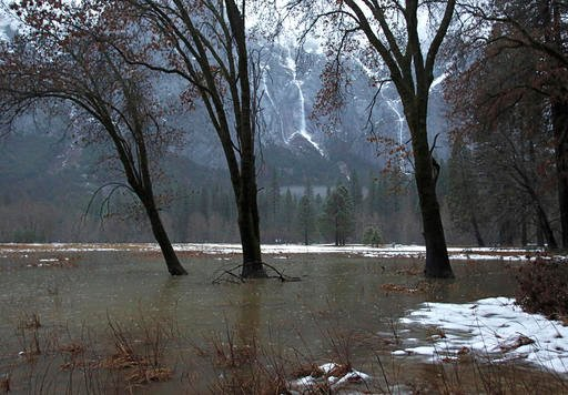 Leidig Meadow, which is normally dry, is flooded by the Merced River Sunday, Jan. 8, 2017, as makeshift waterfalls are are off in the distance from pouring rainfall in Yosemite National Park, Calif.