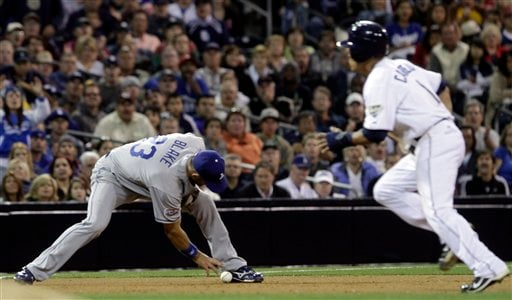 Los Angeles third baseman Casey Blake drops a hit from the San Diego Padres' Jerry Hairston Jr., as Everth Cabrera, right, makes his way to third in the seventh inning during their baseball game Tuesday, July 27, 2010 in San Diego. (AP Photo/Gregory Bull)