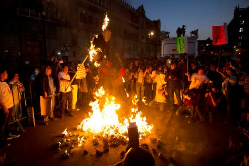 A burning effigy of U.S. President-elect Donald Trump is held aloft as protestors burned representations of Trump and Mexican President Enrique Pena Nieto, during a march by thousands angry at the government.