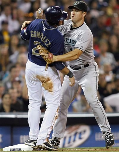 San Diego Padres' Adrian Gonzalez, left, is tagged out at third base by Florida Marlins third baseman Wes Helms during the sixth inning.