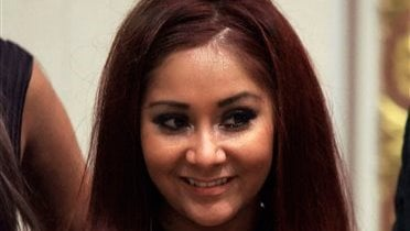 """In this July 27, 2010 file photo, Nicole """"Snooki"""" Polizzi , a cast member of MTV's """"Jersey Shore"""" reality series is shown at the New York Stock Exchange. (AP Photo/Richard Drew, file)"""