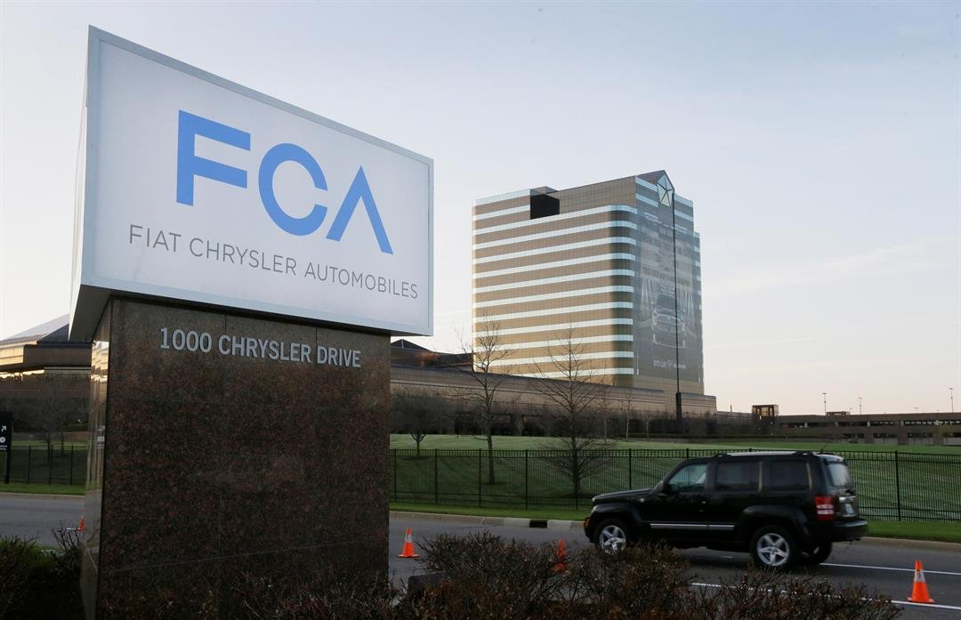 FILE - In this Tuesday, May 6, 2014, file photo, a vehicle moves past a sign outside Fiat Chrysler Automobiles world headquarters in Auburn Hills, Mich. (AP Photo/Carlos Osorio, File)
