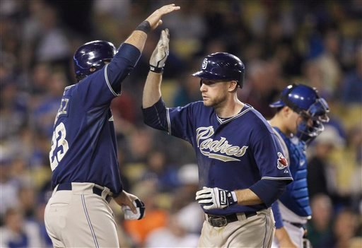 Padres' Chase Headley, right, is congratulated by Adrian Gonzalez, left, after hitting a three-run home run to score Gonzalez and Miguel Tejada as LA Dodgers catcher Russell Martin reacts behind Aug. 2, 2010, in Los Angeles. (AP Photo/Danny Moloshok)