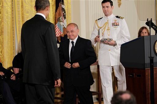 President Barack Obama awards the Presidential Citizens Medal to Jorge Munoz from New York City during a ceremony in the East Room of the White House, Wednesday, Aug. 4, 2010, in Washington.