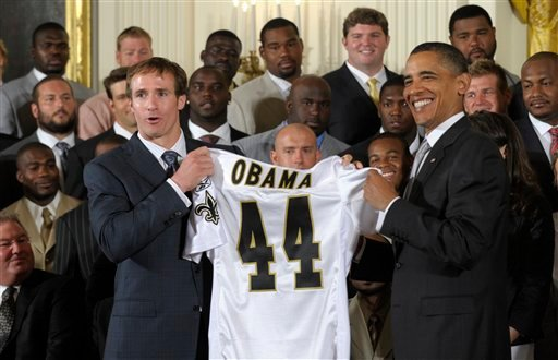 President Barack Obama, right, is presented with a New Orleans Saints football jersey from Saints quarterback Drew Brees, as Obama honored the 2009 Super Bowl Champion New Orleans Saints NFL football team.