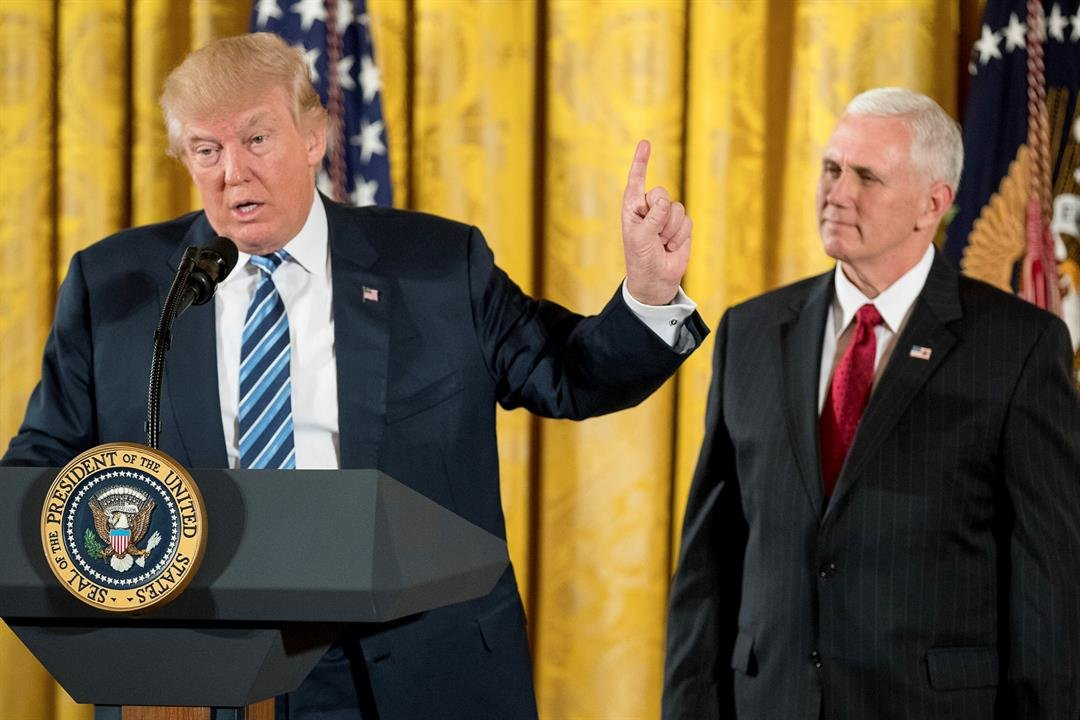 President Donald Trump, accompanied by Vice President Mike Pence, right, speaks during a White House senior staff swearing in ceremony in the East Room of the White House, Sunday, Jan. 22, 2017, in Washington. (AP Photo/Andrew Harnik)